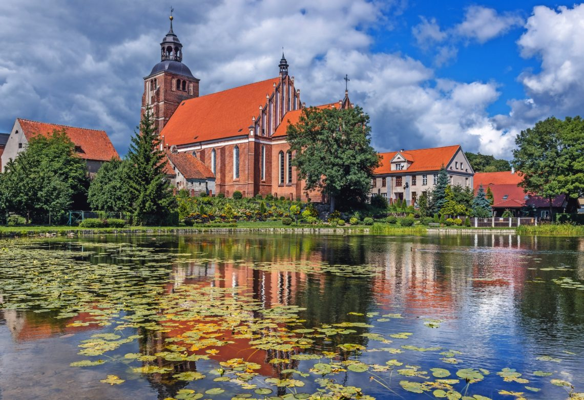 Pond on Pisa River and Saints Anne and Stephen Catholic Church in Barczewo, small city near Olsztyn, Masuria region of Poland